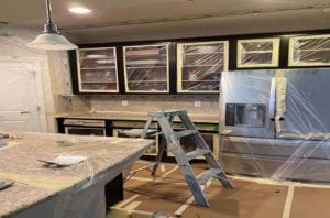 prepped kitchen cabinets covered in plastic and tape
