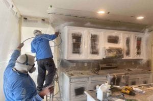 Two paint crew members spraying interior cabinets white
