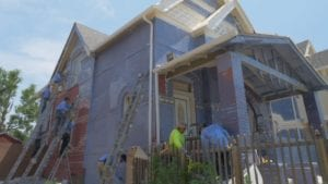 Large paint crew painting an exterior home