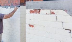 a guy painting brick white