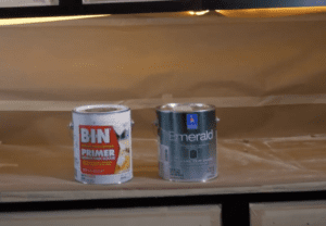 Image of bin shellac primer can next to Sherwin Williams Emerald Urethane paint