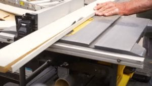 photo woodworking a board through a table saw