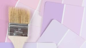 A paint brush laying on top of pink and purple paint color swatches