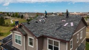 aerial shot of roofers redoing a roof