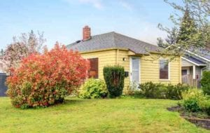 A yellow home with decent yard, landscaping and bluesky