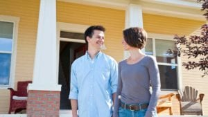 a smiling couple looking at each other and holding hands in front of yellow home
